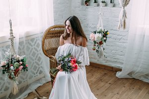 A happy brunette girl with a bunch of flowers sits on a wicker chair. Cheerful, young bride holds a rustic wedding bouquet with peonies.