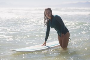 Female surfer standing in the sea with surfboard