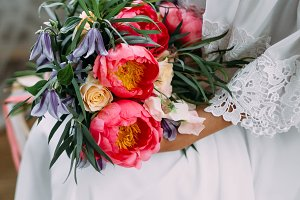 Bride holds in hands a rustic wedding bouquet with white roses and crimson peonies. Close-up