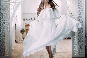 The Beautiful bride is spinning around herself in dance. Cheerful brunette is posing in fluttering dress in a vintage room. Wedding
