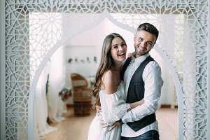 A cheerful bride and groom with a cute smile laughing and embracing. Beautiful newlyweds posing in vintage room