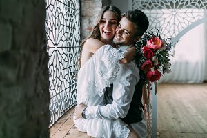 Beautiful and cheerful newlyweds laughing and embracing near the vintage window