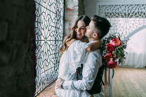 Cheerful young bride hugging groom while he kisses her in cheek and embraces her waist on the windowsill