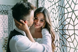 Cheerful young bride embraces groom's head while he kisses her in cheek on the vintage window background