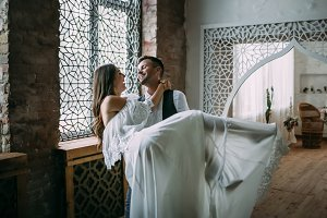 Groom is spinning around with bride on his arms. Beautiful newlyweds posing in a vintage room. Wedding