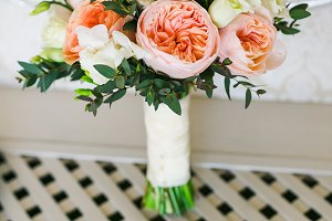 Bridal bouquet near the white vintage wall on the white wooden floor