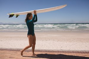 Female surfer walking with surfboard on her head in the beach