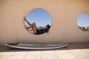 Female surfer relaxing on the circular window