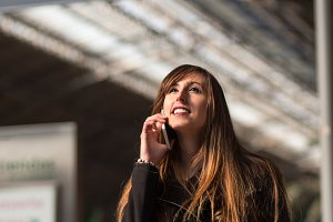 young woman talking on the phone in a station