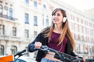 young woman listening to music in the street