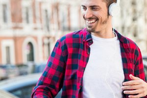 attractive young man listening music outdoors