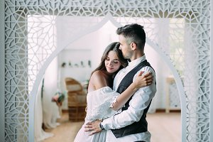Cheerful young bride smiling and hugging groom while he kisses her in the head and embraces her waist. Beautiful newlyweds posing in vintage room
