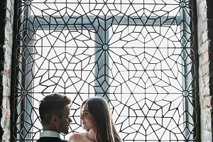 Beautiful young newlyweds are posing on the ornament vintage window background. Low-key. Artwork. Wedding