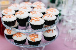Cupcakes with initials of the bride and groom on a two-level stand at a wedding