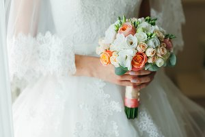 An unrecognizable bride is standing near the window and holding a wedding bouquet with white and peach roses. Close-up