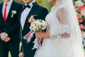 The Beautiful bride holds a wedding bouquet with pink roses and peonies. Wedding ceremony in process