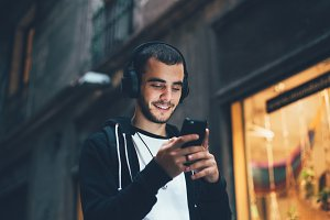 Young man with headphones uses phone