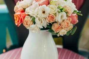 Wedding bouquet of white and peach roses in a glass vase on the classic wooden chair. Artwork