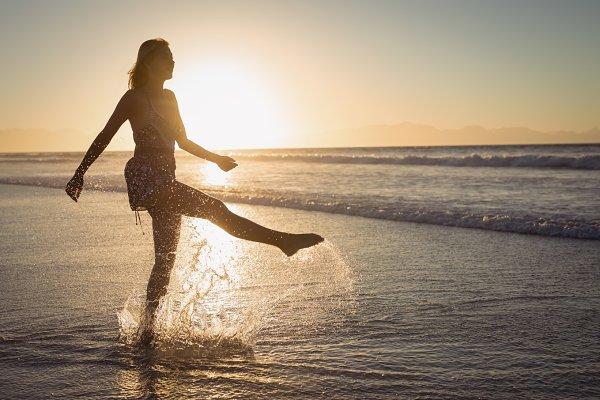 Silhouette woman splashing water on…