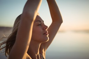 Close up young woman doing yoga at beach