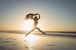 Silhouette woman holding scarf while jumping at beach