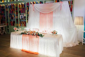 Festive table for the bride and groom decorated with lights, cloth, and flowers