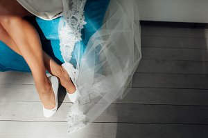 The beautiful bride in white wedding shoes is sitting on a blue chair. Slim and tanned legs of a young lady in light of the sun.