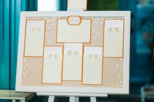 Wedding seating chart on the easel in the park.