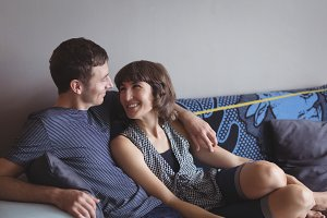 Couple relaxing on sofa in living room at home