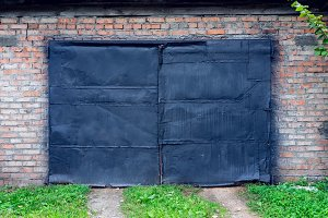 Old painted black paint on garage in nature. Black door in a building against a brick wall. A green lawn path leads to the door.