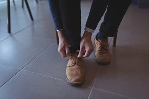 Man tying shoe lace in living room