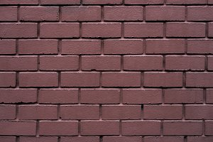 Brick wall made of red stone background. The spoiled brick is vintage.