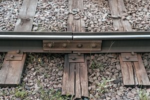 Old sleepers, in city there is a tram line. In nature, a wet wooden board. Coupling of metal rails.