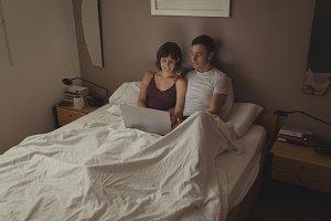 Couple using laptop in bedroom