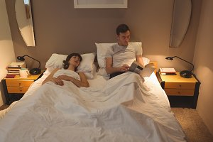 Man reading book while woman resting on bed