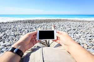 Tourist Lying On The Beach With Phone
