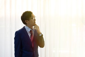 Young thoughtful business man with glasses on thinking over white background with the light coming from the window