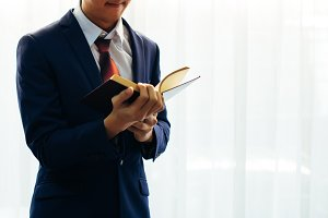 Young man in formal suit reading a book over white background with copy space