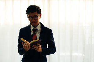 Young Asian man in glasses in formal suit reading the book in the room over white background with copy space