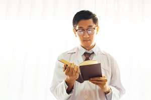 Smart doctor physician in glasses in medical gown, reading a book over white background with copy space