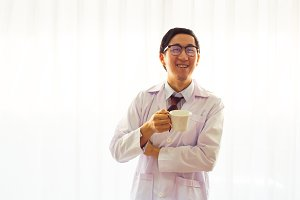 Smiling doctor in gown holding a cup in the hospital near window