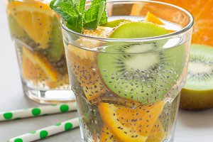 Healthy detox chia seed drink with kiwi, orange and mint in glass, square format