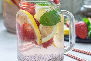 Healthy detox chia seed drink with strawberry, lemon and mint in glass jar, square format