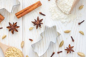 Christmas background with different spices, flour and cookie cutters on white wooden table, top view, square format