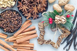 Different kinds of aromatic winter spices in bowls and on gray concrete background, top view, horizontal