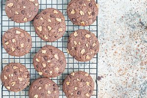 Homemade chocolate cookies with walnuts and chocolate chips on cooling rack, horizontal, top view, copy space