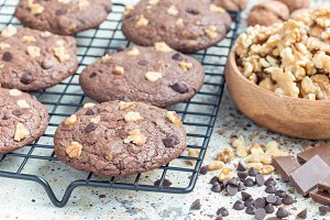Homemade chocolate cookies with walnuts and chocolate chips on cooling rack, horizontal