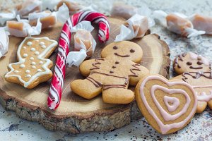 Sweet gifts for holiydays. Homemade christmas gingerbread cookies and caramel candies on wooden board, horizontal