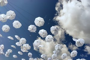 White umbrellas on blue sky background