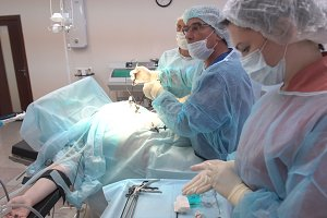 Surgeons team working with Monitoring of patient in surgical operating room. Operation using laparoscopic equipment. Hospital.